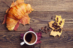 Coffee, croissant and autumn leaves Royalty Free Stock Photo