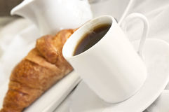 Coffee and croissant. Black coffee and a croissant served to bed - a french breakfast Royalty Free Stock Photo
