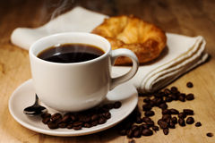 Coffee,croissant and coffee bean on wooden table Stock Photos