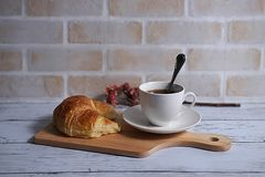 Coffee and croissant. A cup of coffee and croissant on wooden board in brick wall background Royalty Free Stock Photos