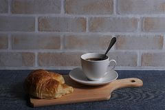 Coffee and croissant. A cup of coffee and croissant on wooden board in brick wall background Royalty Free Stock Photo