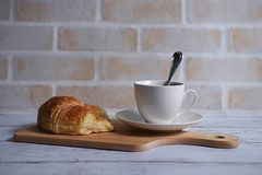 Coffee and croissant. A cup of coffee and croissant on wooden board in brick wall background Stock Photos