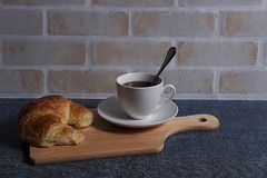 Coffee and croissant. A cup of coffee and croissant on wooden board in brick wall background Stock Photo