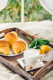 Coffee, croissant and flowers on bed Stock Photography