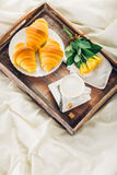 Coffee, croissant and flowers on bed Stock Photo