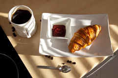 Coffee, croissant and jam - french breakfast. In the morning sun Stock Images