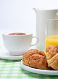 Coffee Croissant and Juice Breakfast. A breakfast setting  of croissant, orange juice and coffee on a green gingham table cloth Royalty Free Stock Photos