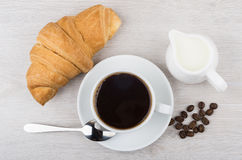 Coffee, croissant, milk jug and coffee beans on table. Black coffee, croissant, milk jug and coffee beans on wooden table. Top view Royalty Free Stock Image