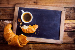 Coffee and a croissant on an old school slate Royalty Free Stock Images