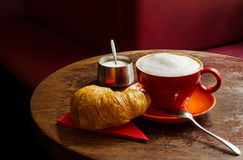 Coffee with croissant and sugar bowl in a cafe. A cozy coffee scene in a cafe awaiting to be consumed Stock Photos