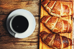 Coffee and croissant. On wooden background Royalty Free Stock Photo