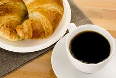 Coffee and a croissant on wooden counter. Stock Photo