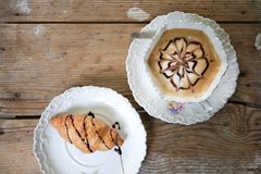Coffee and croissant on wooden table Stock Photos