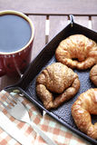 Coffee and croissants closeup. Coffee breakfast with croissant closeup in leather nest Stock Photo