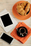 Coffee with croissants, smartphone, e-book and a notepad. Royalty Free Stock Images