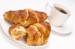 Coffee and Croissants on a white background. Two croissants on a white plate with coffee in a white cup in the background royalty free stock photo