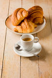 Coffee and croissants on wooden table Stock Photos