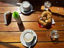 1 Coffee and croissants on a wooden table. Two coffees with four croissants and two glasses of soda on a brown table Royalty Free Stock Photography