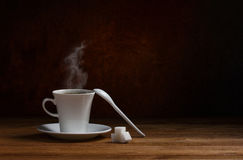 Coffee and cubes sugar. Coffee with steam in white  cup on saucer, ceramic spoon and cubes sugar on wooden table on dark brown background Stock Photo