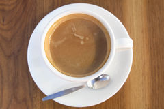 Coffee Cup. China coffee cup and saucer on wooden table surface with teaspoon Stock Photos