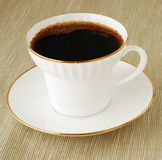 Coffee cup. White porcelain cup with hot fresh coffee on a linen napkin royalty free stock photo
