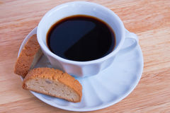 Coffee cup. A cup of coffee with two biscotti on a natural wood table Stock Photos