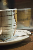 Coffee cup. Closeup of a coffee cup, saucer and spoon on a wooden table with a reflective surface behind it Royalty Free Stock Photo