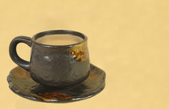 Coffee cup. Brown ceramic coffee cup on a light brown background Stock Image