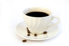 Coffee cup. And coffee beans over a white background Stock Photos