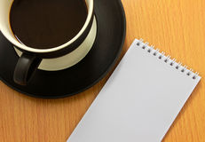 Coffee cup. And white notebook Royalty Free Stock Photos