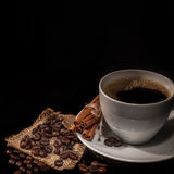 Coffee cup. Cup of black coffee flavored with cinnamon, cinnamon sticks and coffee beans Royalty Free Stock Image