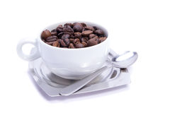 Coffee cup. Coffee beans poured into white coffee cup. Isolated on white Royalty Free Stock Image