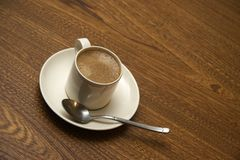 Coffee Cup. A coffee cup located on a wooden table Royalty Free Stock Images