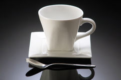 Coffee cup. Empty coffee cup with reflection isolated on toning black background Stock Photos