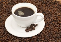 Coffee cup. White coffee cup with black coffee and coffee beans on brown background stock photo