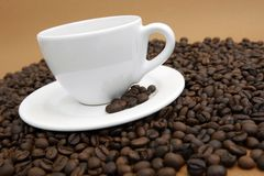 Coffee cup. White coffee cup with black coffee and coffee beans on brown background stock image