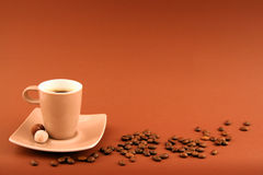 COFFEE CUP. With coffee-beans on toning brown background Royalty Free Stock Photos