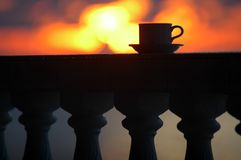 Coffee cup. On a fence in front the morning sun Stock Photo