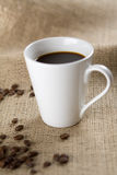 Coffee Cup. White coffee cup with roasted coffee beans on sackcloth. Shallow depth of field stock images
