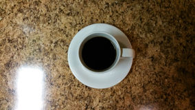 Coffee cup from above. White coffee cup and saucer from above on brown granite Stock Images