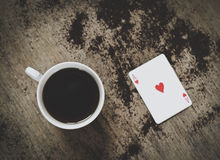 Coffee cup and ace of hearts. On a table stock image
