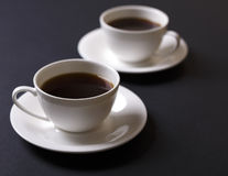 Coffee in a cup against a dark background. Two cups of hot coffee against a dark background Royalty Free Stock Photo