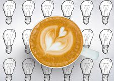 Coffee cup against white background with lightbulbs Royalty Free Stock Photos