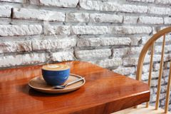 Coffee cup against white brick wall royalty free stock photos