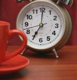 Coffee cup and alarm clock Stock Photos
