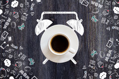 Coffee cup alarm clock. Sketch on dark wooden desktop with communication drawings Stock Photo