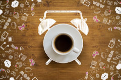 Coffee cup alarm. Clock sketch on wooden desktop with communication drawings Royalty Free Stock Photography