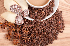 Coffee cup, anise on coffee beans, sweets on the wooden background Royalty Free Stock Images