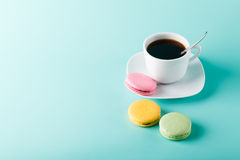 Isolated photo of coffee with macaroons. On aqua background with place for an inscription Stock Images