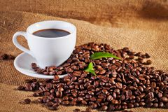 Coffee cup and arabica beans on cloth sack Stock Photos